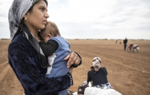 A Syrian woman holding her infant waits near an informal border crossing to go back to Kobane, Syria, despite ongoing clashes between ISIS and Kurdish fighters. Many Syrian Kurds are finding Turkey expensive and inhospitable.