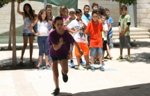 The kids at Project Harmony camp mostly do normal summer activities, like sports tournaments, as a way to get to know each other. Here, children compete in a jumping contest.