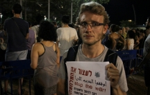 """Israeli Yasha Marmer protests against his country's operation in the Gaza Strip, holding a poster that says """"stop the war"""" in Hebrew, Arabic and English."""