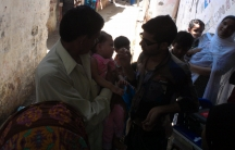 A child is immunized against polio at a makeshift clinic in the poor Karachi neighborhood called Hijrat.