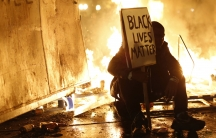 A demonstrator sits in front of a street fire during a demonstration following the grand jury decision in the Ferguson, Missouri shooting of Michael Brown, in Oakland, California on November 25, 2014.