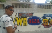 Freshla in front of a mural he commissioned in Delmas 5, Haiti