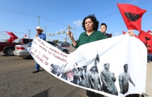 Woman on street holds sign showing farmworkers marching in black and white photo