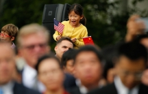 A girl holds a US and a Chinese flag during the arrival ceremony for China's President Xi Jinping and first lady Madame Peng Liyuan at the White House in September, 2015.