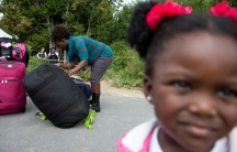 A mother and her young daughter are watched by Royal Canadian Mounted Police (RCMP) officers as they prepare to cross the US-Canada border from New York into Quebec earlier this month. Like thousands of others fleeing the US for Canada, the woman told off