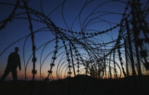 A soldier walks past concertina wire surrounding the outside of Joint Task Force Guantanamo's Camp Delta at the US Naval Base in Guantanamo Bay.