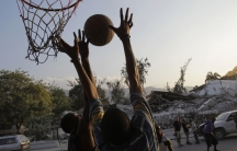 Survivors of Haiti's earthquake play basketball in front of a pile of debris of the justice palace in Port-au-Prince.