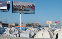 A Haitian city, juxtaposed with a billboard featuring the Statue of Liberty