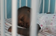 A Haitian child who will be placed for adoption sleeps in his crib at an orphanage outside of Port-au-Prince.