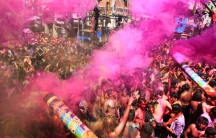 Men dance as others spray colored powder on them during Holi celebrations in India.