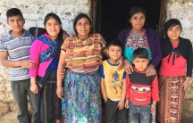Elvira Mauricia Diaz standing center with her family against a stone wall backdrop.