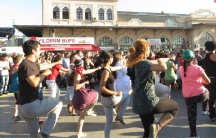 Flash mob protesters perform near an outdoor concert, just outside one of Istanbul's heavily used ferry stations.