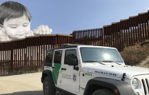 Large photo installed on one side of metal fencing looks out over Border Patrol SUV