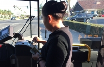 Woman putting bills in public bus machine, with windshield behind her