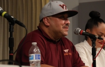 Man in baseball cap, close up, sitting at table with microphone and other panelists.