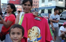A woman in Plaza Miranda, outside Quiapo Church in Manila, sells off her dwindling stock of Pope Francis t-shirts in advance of the Pope's visit to the Philippines.