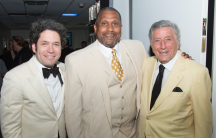 Tavis Smiley, center stands backstage with Gustavo Dudamel and Tony Bennett.