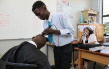 Students at COSAT shave each other's heads