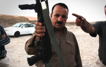 A Kurdish fighter shows off his new weapons outside the gun bazaar. Behind him is the prison that sits next to the market.