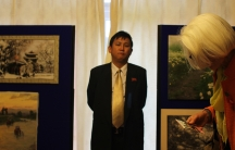 A North Korean official in London watches over visitors to the embassy's art exhibition