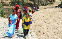 Women community health workers in Dolakha district walk up the hill for a monthly meeting inside the under-construction health center. The new building will replace the clinic destroyed in the earthquake last year.