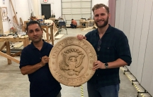 Najibullah Zahedi (left) is a refugee from Afghanistan who resettled in Georgia with his family. He's a student at the Lantern Project, run by Luke Keller, where he carved the US Congress seal.