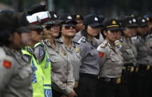 Female Indonesian police officers stand guard outside the presidential palace during a protest against the recent fuel price hike in Jakarta on November 19th, 2014.