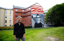 Steffen Kverneland stands in front of a large mural in the Tøyen neighborhood of a Oslo created from the cover of his graphic biography of Edvard Munch. The mural was created by Knverneland and another Norwegian, Monica Tollnes.