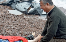 An Iraqi man mourns his wife on the beach on Lesbos on October 15, 2015.