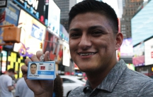Man holding up ID card for medical school