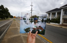 Photographer Carlos Barria holds a print of a photograph he took in 2005, as he matches it up at the same location 10 years on, in New Orleans. The print shows Errol Morning sitting on his boat on a flooded street September 5, 2005, after Hurricane Katrin