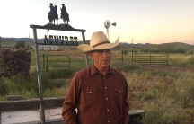 Man standing in front of ranch sign and American flag