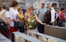 Visitors to the new Space of Synagogues memorial place stones in remembrance of the dead in Lviv, Ukraine on Sept. 4.