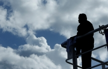 A migrant looks out to sea off the coast of Libya.