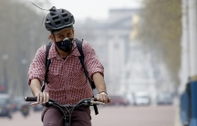 A cyclist wears a mask as he cycles near Buckingham Palace in London April 2, 2014. Britain's Meteorological Office forecast that London would be affected by smog this week, caused by powerful dust storms and strong winds in the Sahara.