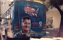 "An advertisement for ""Los Otros Mexicanos"" featuring Betto Arcos is plastered on a bus."