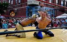 Man in wrestling ring being tackled with referee in background
