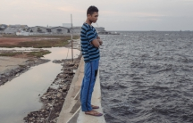 """Feri Yadi, a resident of Muara Baru in North Jakarta, stands atop the seawall recently built to protect his neighborhood. He has little confidence that the wall will work as expected. """"Like in the past, this will be broken somehow"""" he says."""