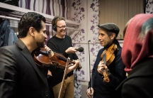 Arash Jame offers Marco Werman a violin lesson on Iranian scales.