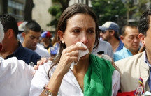Venezuelan opposition leader Maria Corina Machado reacts after inhaling tear gas after she tried to take a seat at the national assembly in Caracas April 1, 2014.