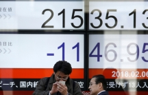 A man looks at a mobile phone in front of an electronic board showing Japan's Nikkei average outside a brokerage in Tokyo, Japan.