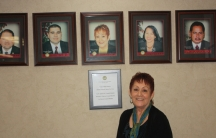 """Former farmworker and current Delano Mayor, Grace Vallejo, stands in front of photos of her fellow city council members. The city council is made up of all Hispanic members. """"That's a huge change from back in the 1960s. We've come a long way."""" she says. V"""