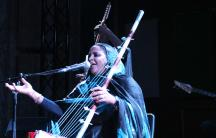 Noura Mint Seymali, with her husband Jeiche Ould Chighaly behind her, playing at the Issue Project Room in Brooklyn on her first US tour.