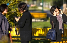 North Koreans chat on mobile phones and take some pictures as they enjoy nice weather in a park in central Pyongyang on October 11, 2015.