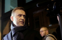 Russian opposition leader Alexei Navalny wearing a dark overcoat and scarf looks left toward a camera.