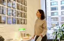 A woman looks at photographs on the wall.