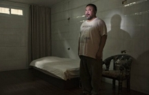 Artist Ai Weiwei stands in an exact replica of the cell where he was detained by the Chinese government for roughly three months in 2011.