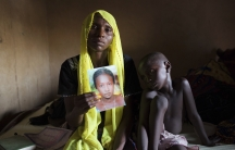 Rachel Daniel, 35, holds up a picture of her abducted daughter Rose Daniel, 17, as her son Bukar, 7, sits beside her at her home in Maiduguri in northeast Nigeria on May 21, 2014. Rose is one of the more than 200 of her classmates on April 14 by Boko Hara