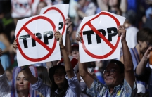 Delegates protesting against the Trans Pacific Partnership (TPP) trade agreement hold up signs during the first sesssion of the Democratic National Convention in Philadelphia. , Pe