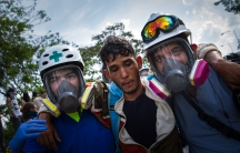 In Venezuela, two volunteers help a protester overcome by tear gas. The volunteers are mostly medical students who provide first aid at the anti-government demonstrations.
